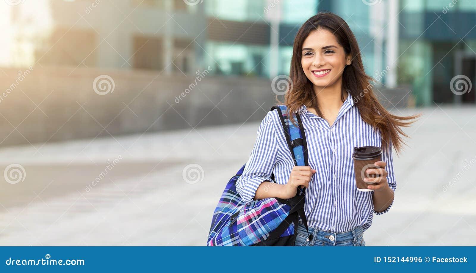 Młoda uśmiechnięta kobieta trzyma filiżanka kawy z plecakiem nad jej ramieniem kosmos kopii