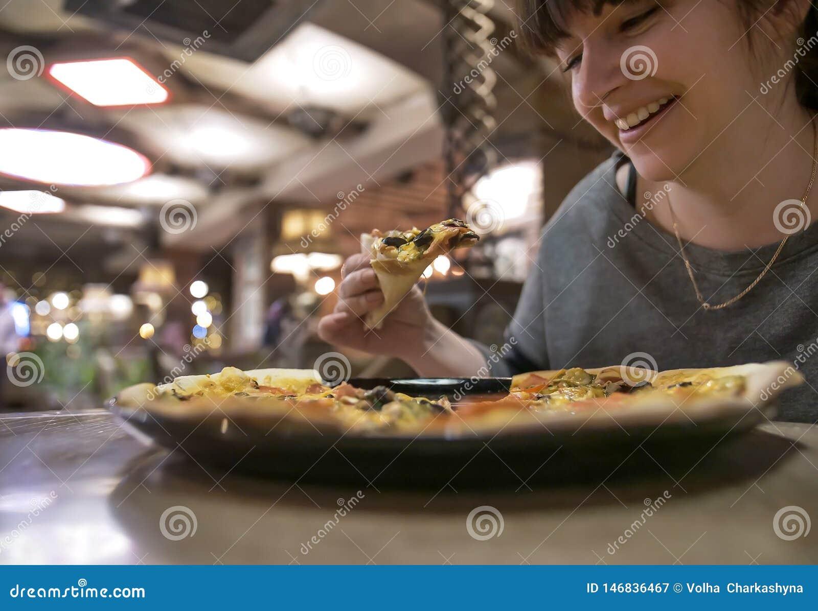 Młoda uśmiechnięta kobieta trzyma plasterek pizza podczas gdy siedzący w kawiarni, w górę