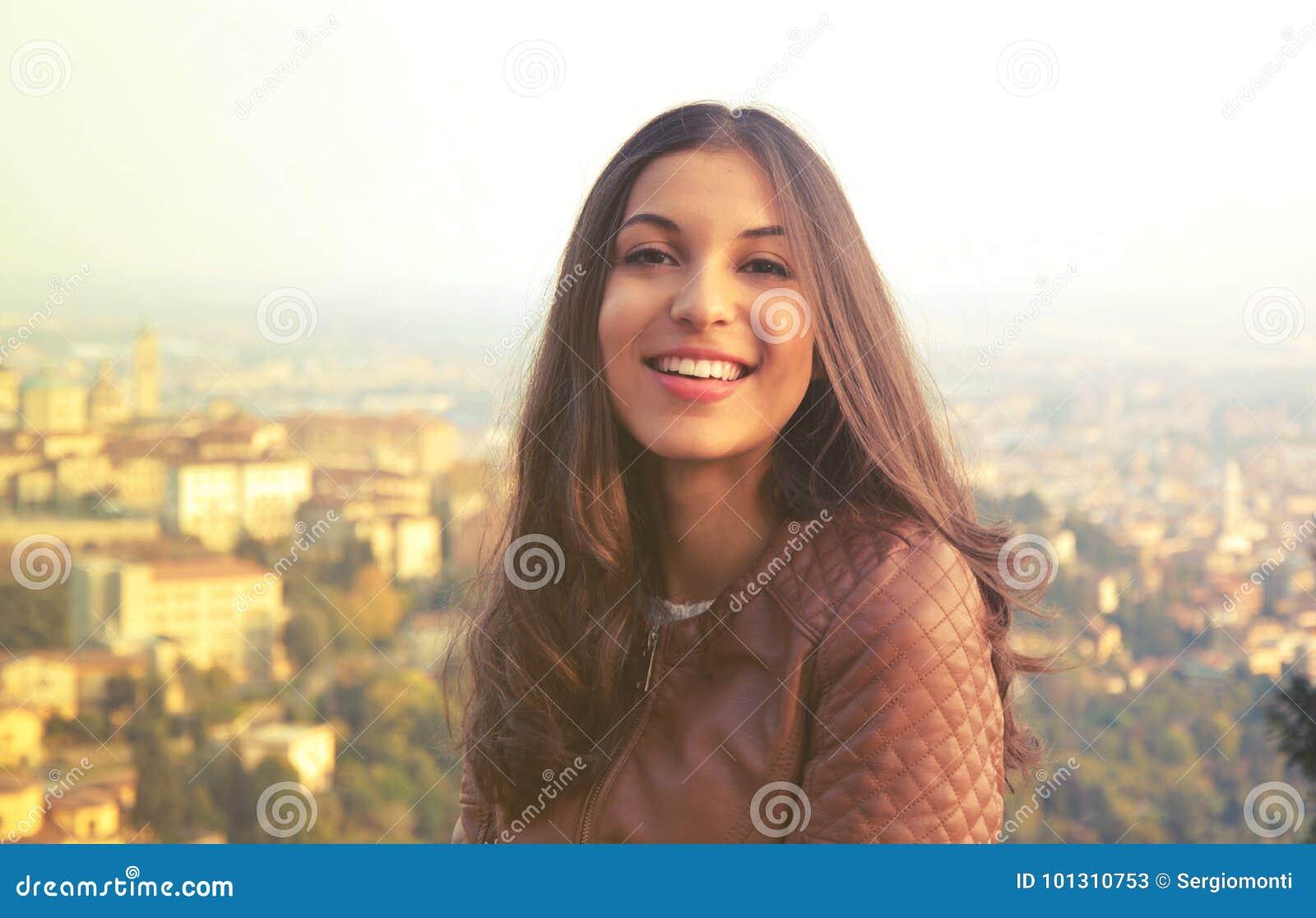 Młoda ufna uśmiechnięta kobieta patrzeje kamerę plenerową przy zmierzchem