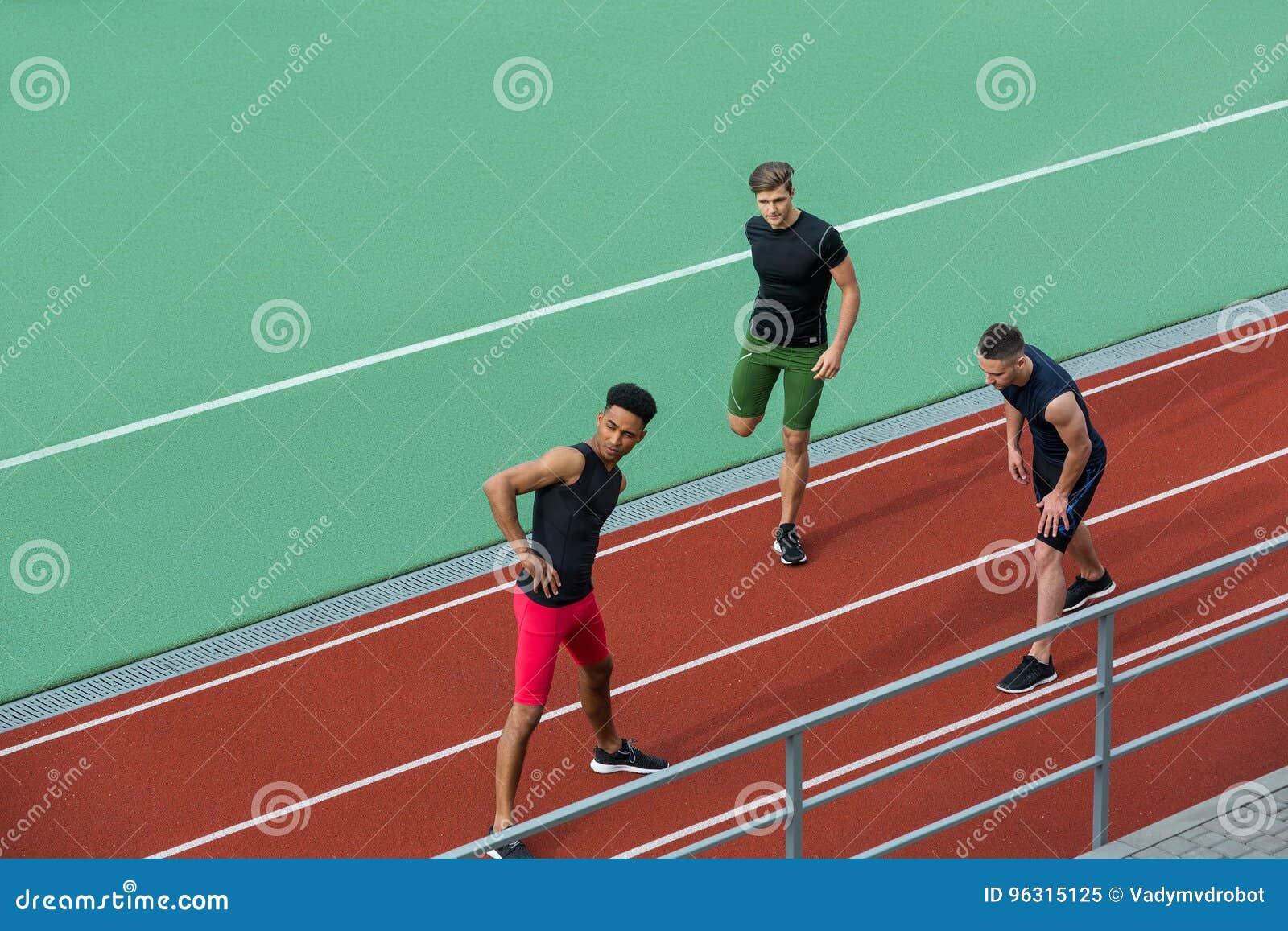 Młoda wieloetniczna atlety grupa robi rozciągań ćwiczeniom
