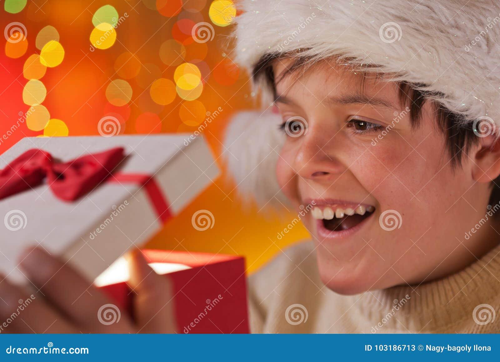 Młoda z podnieceniem nastolatek chłopiec otwiera jego boże narodzenie teraźniejszość