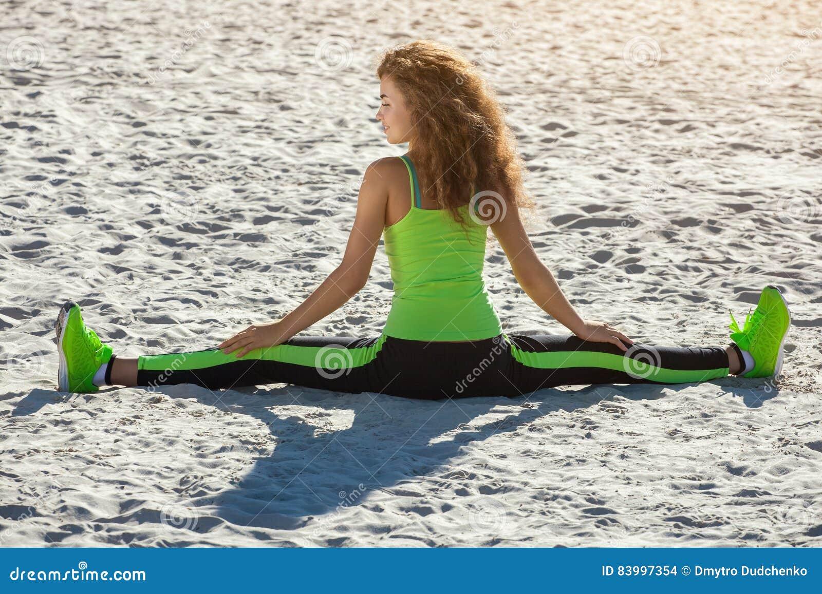 Młode atlety - gimnastyczka z kędzierzawym włosy, jasnozielonym kostiumem i sneakers robi rozłamom na plaży w lecie, ranku ćwicze