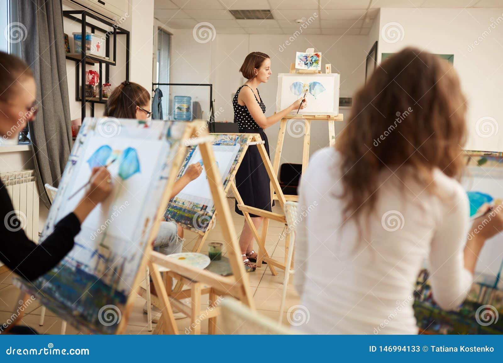 Młode dziewczyny i rysunkowi nauczyciel farby obrazki siedzi przy sztalugami w sztuki studiu
