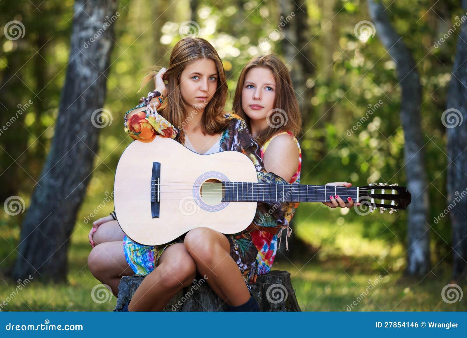 Młode dziewczyny z gitarą na naturze