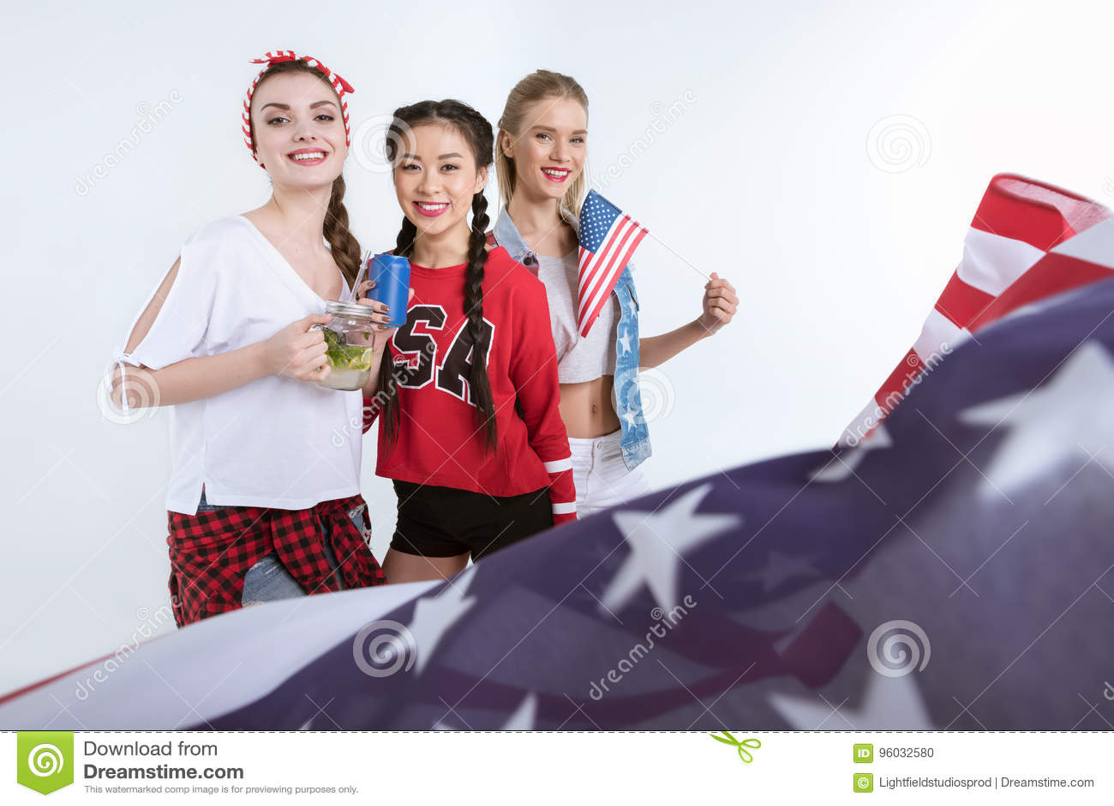 Młode kobiety patrzeje kamerę i pije napoje z flaga amerykańską