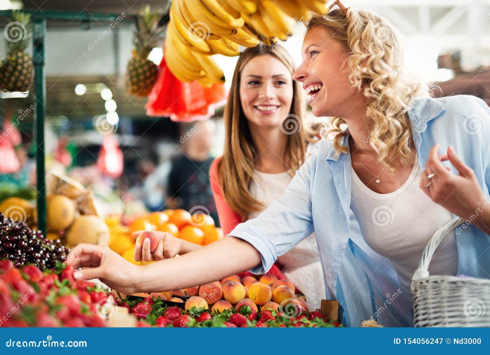 Młode kobiety robi zakupy na targowych zdrowych owoc i warzywach