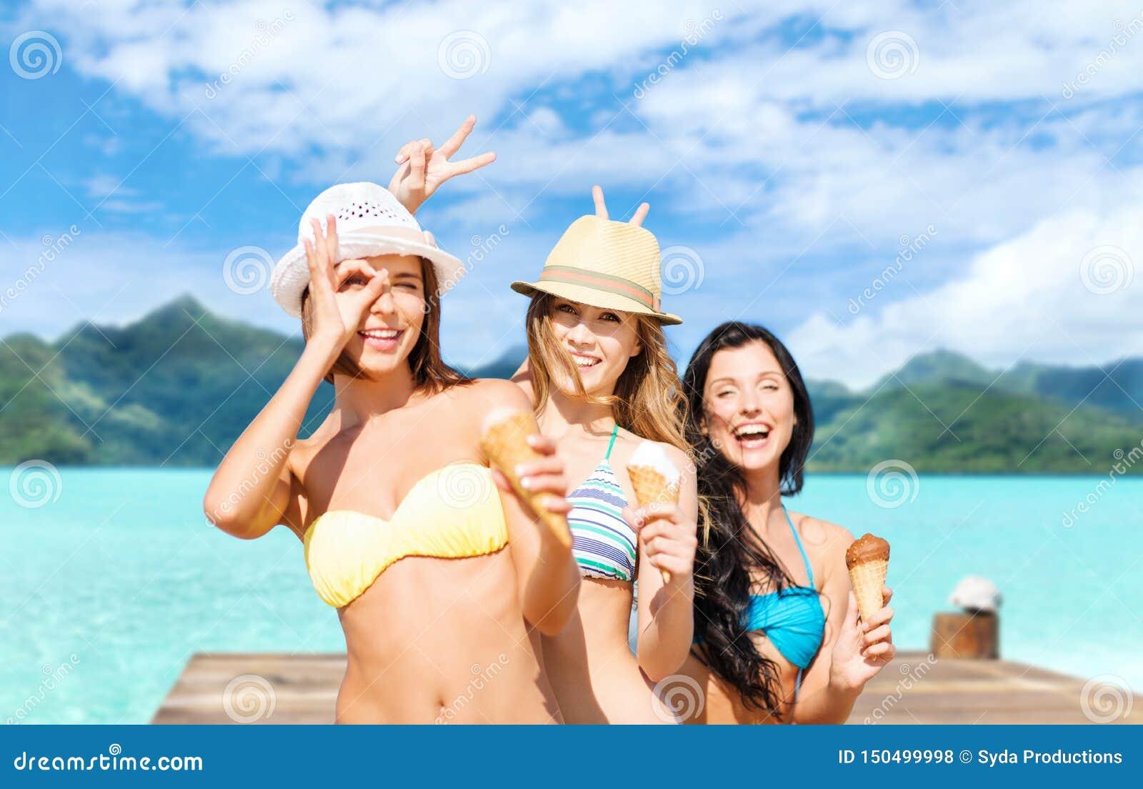 Młode kobiety w bikini z lody na plaży