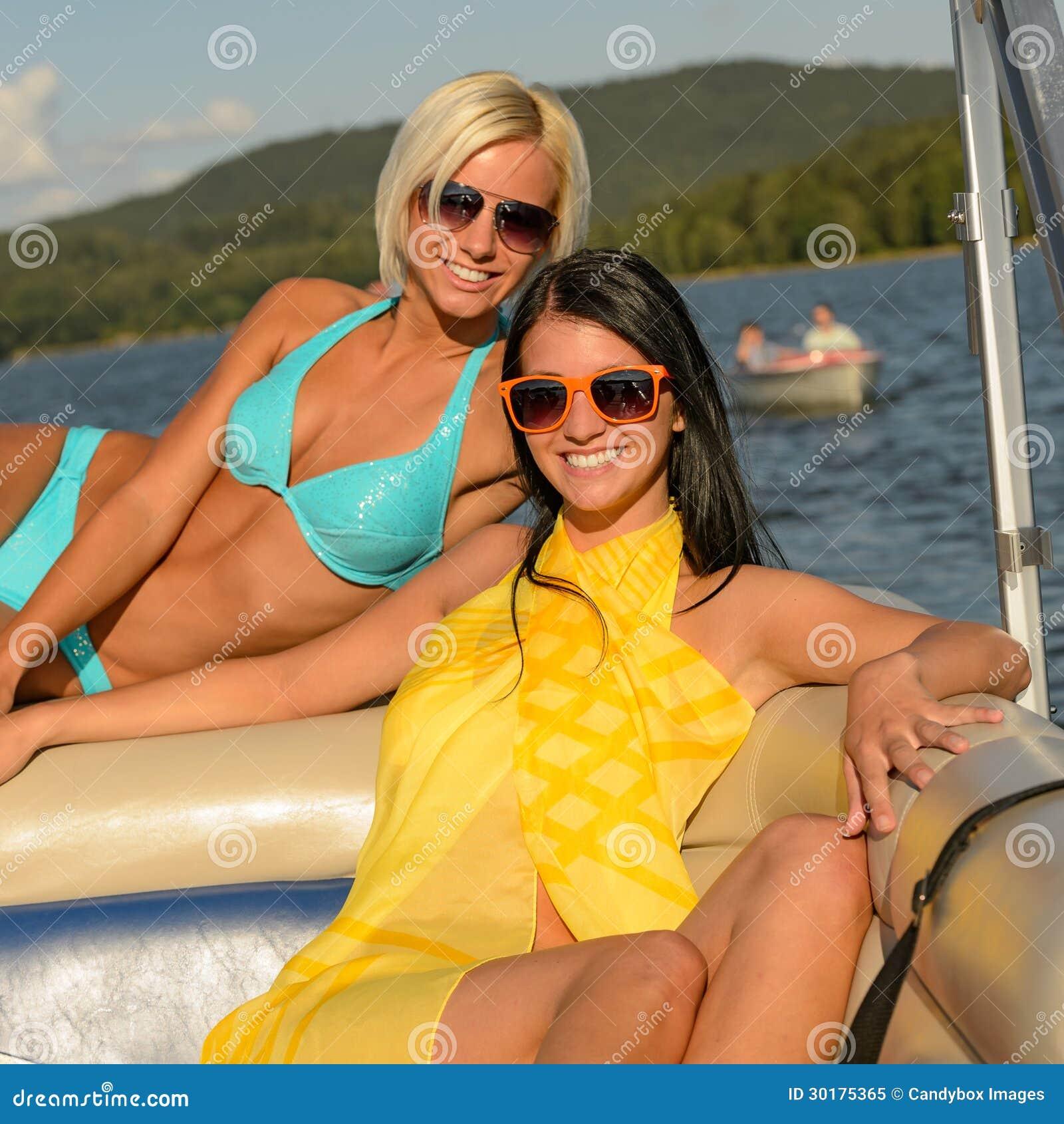 Młode uśmiechnięte kobiety sunbathing na łodzi