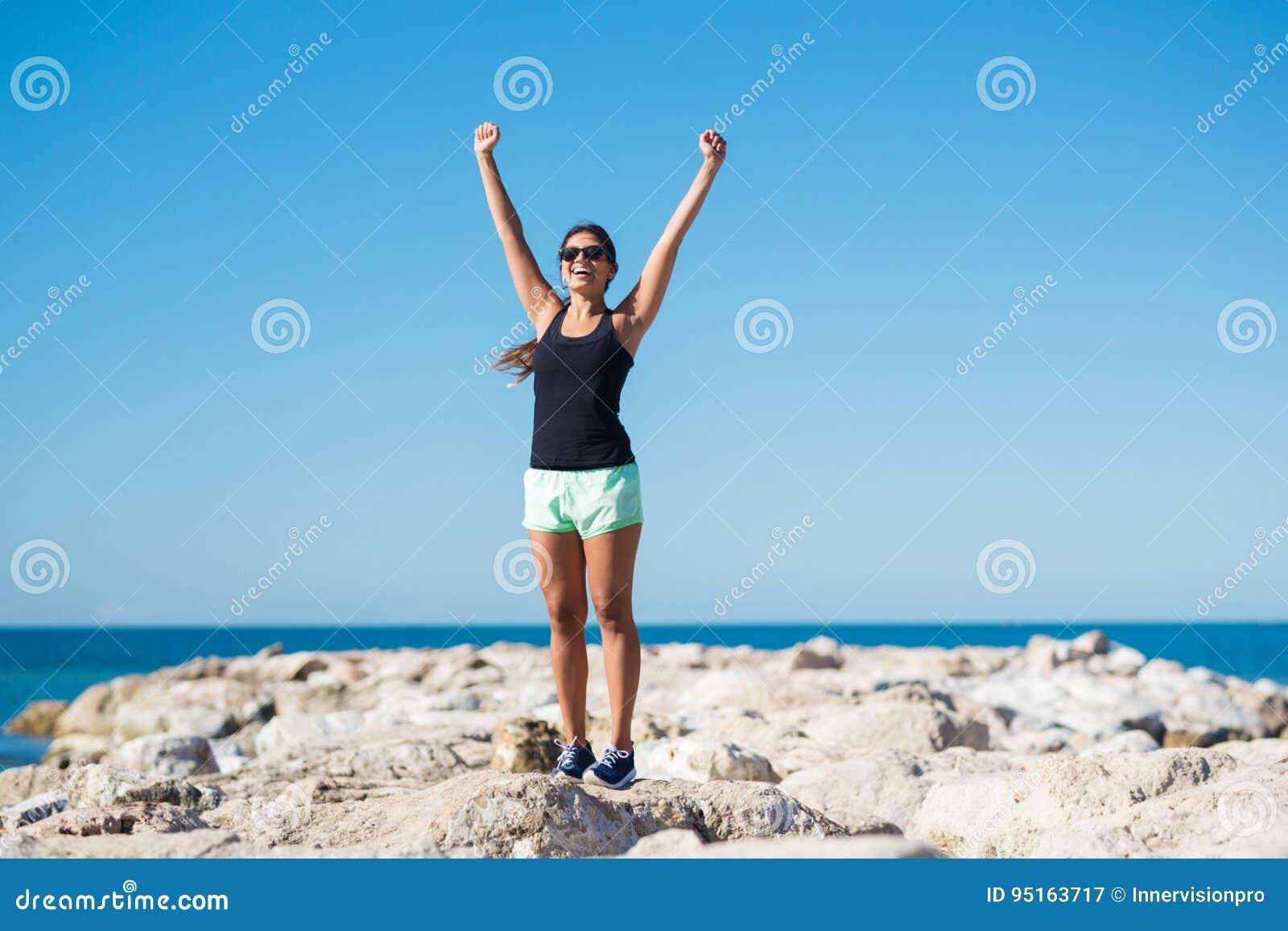 Młode szczęśliwe kobiety wydźwignięcia ręki w zwycięstwie gestykulują