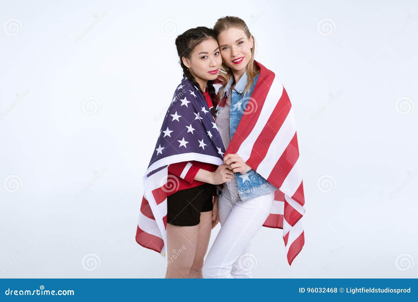 Młode wieloetniczne dziewczyny stoi wpólnie i patrzeje kamerę z flaga usa