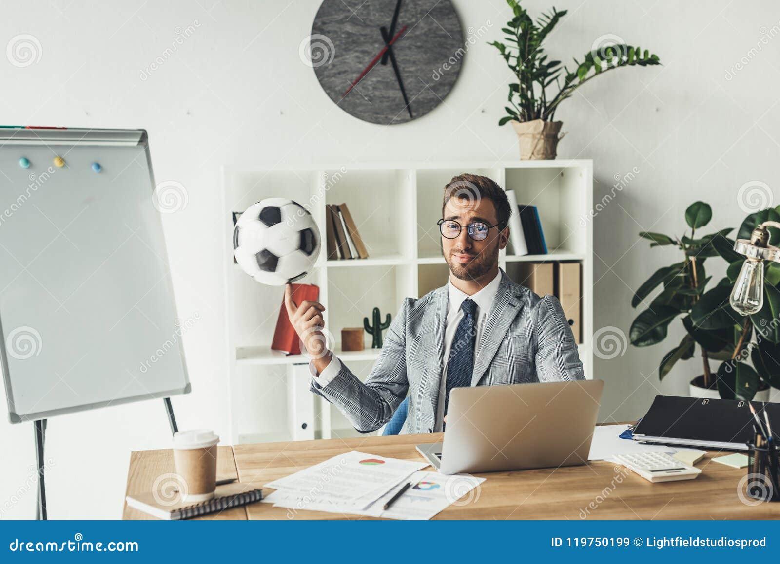Młodego biznesmena piłki nożnej przędzalniana piłka na palcu