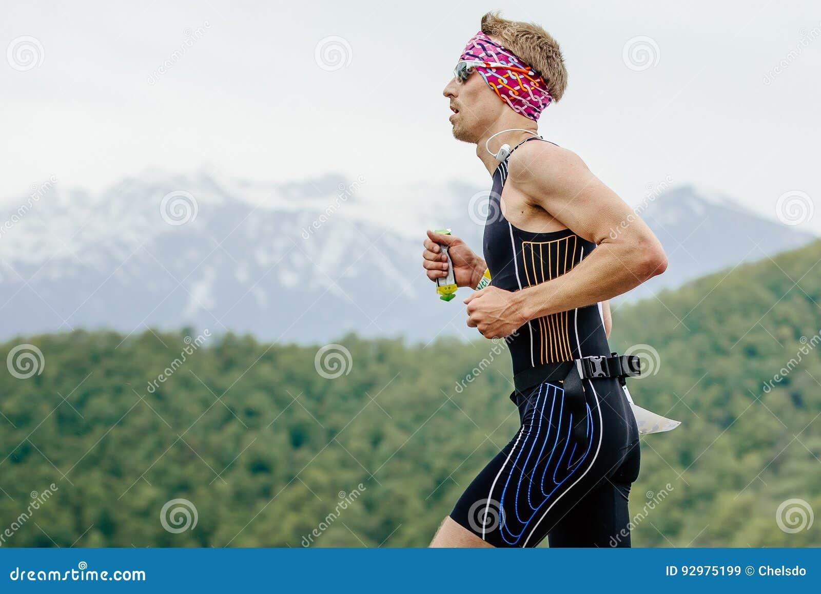 Młodego człowieka biegacz z energetycznym odżywki gel w ręka bieg