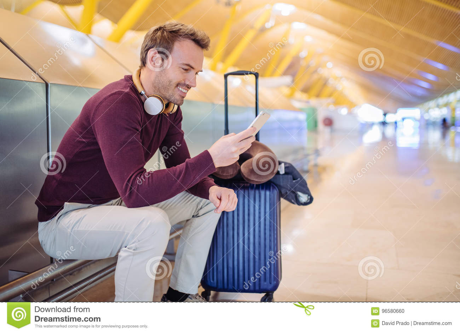 Młodego człowieka czekania słuchająca muzyka i używać przy telefon komórkowy
