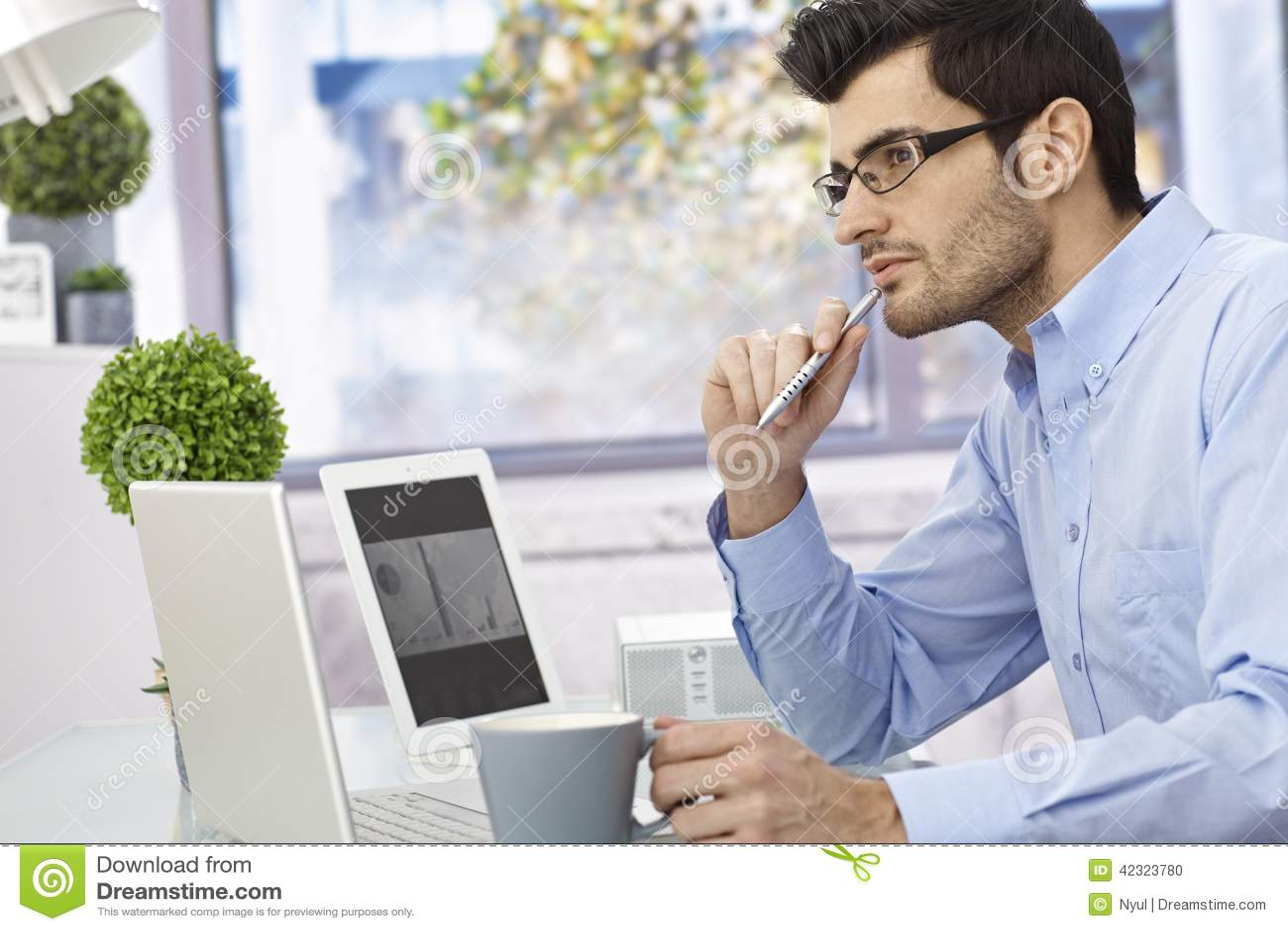 Młodego człowieka główkowanie przy biurkiem