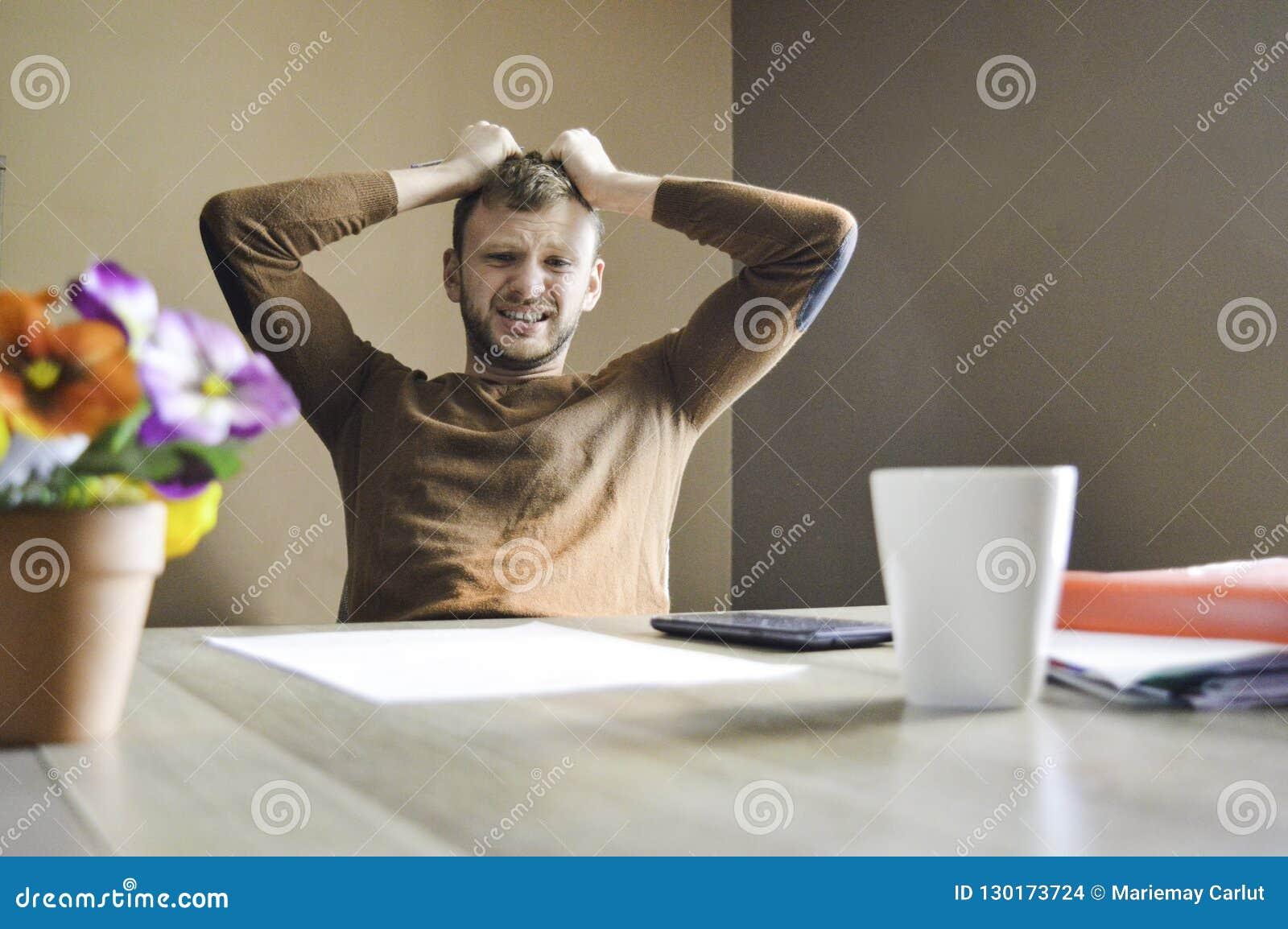 Młodego człowieka gniewny i smutny pracujący mocno na papierkowej robocie i rachunkach w domu