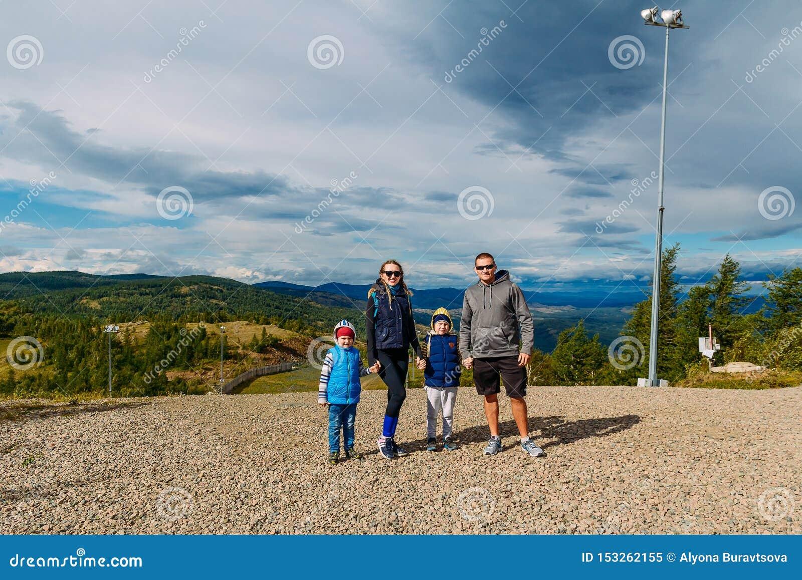 Młodego człowieka, kobiety i dwa dzieci stojak na górze przeciw błękitnemu chmurnemu niebu