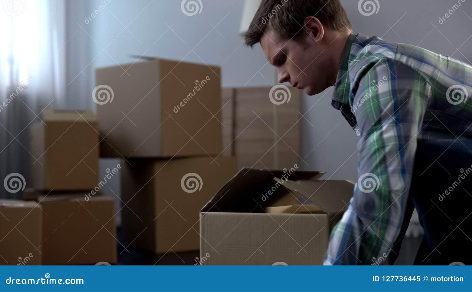 Młodego człowieka kocowania rzeczy w kartonach, rusza się od dormitorium swój dom