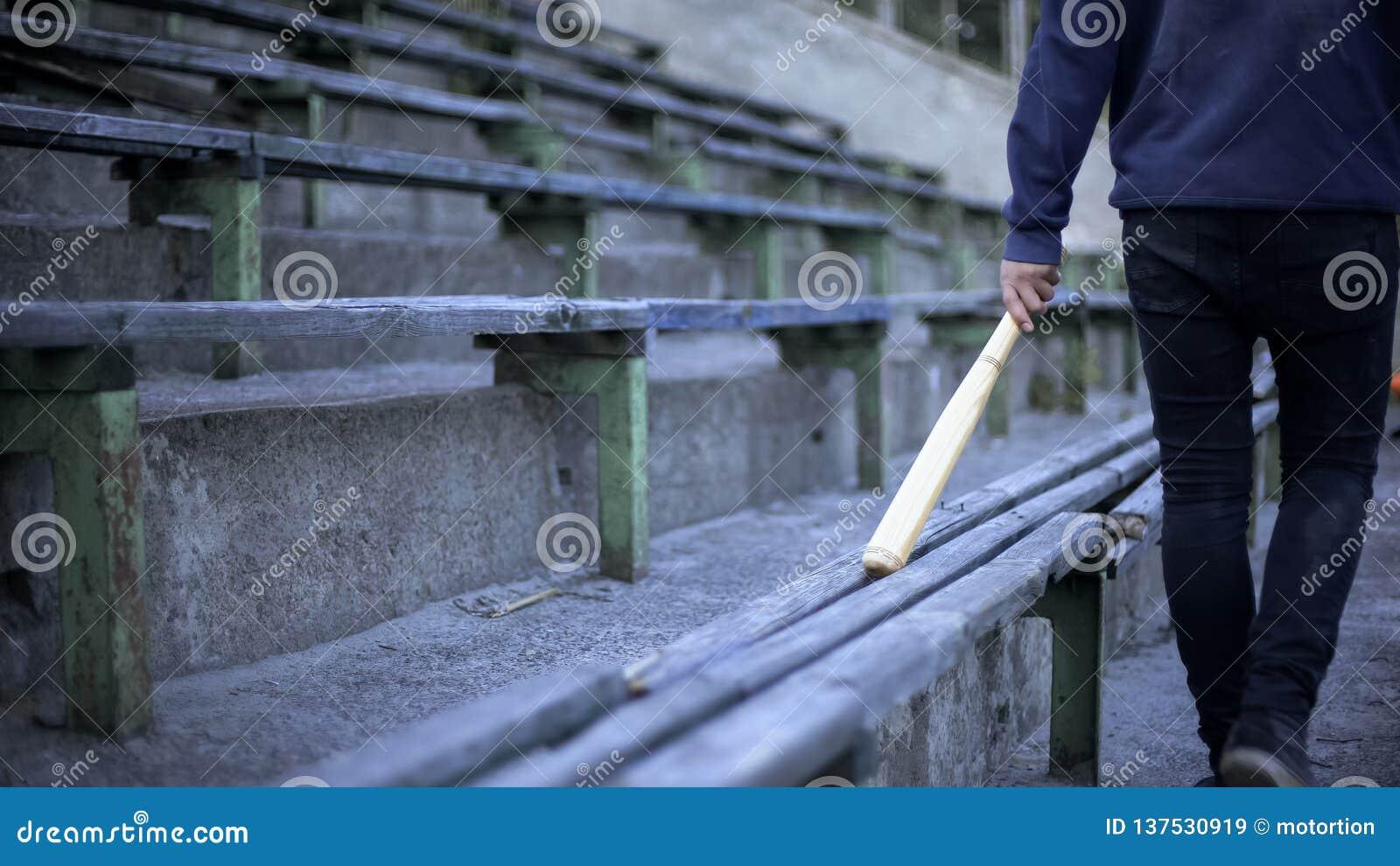 Młodego człowieka odprowadzenie na stadium trybunie z kijem bejsbolowym, gang młodocianych przestępców, wandalizm