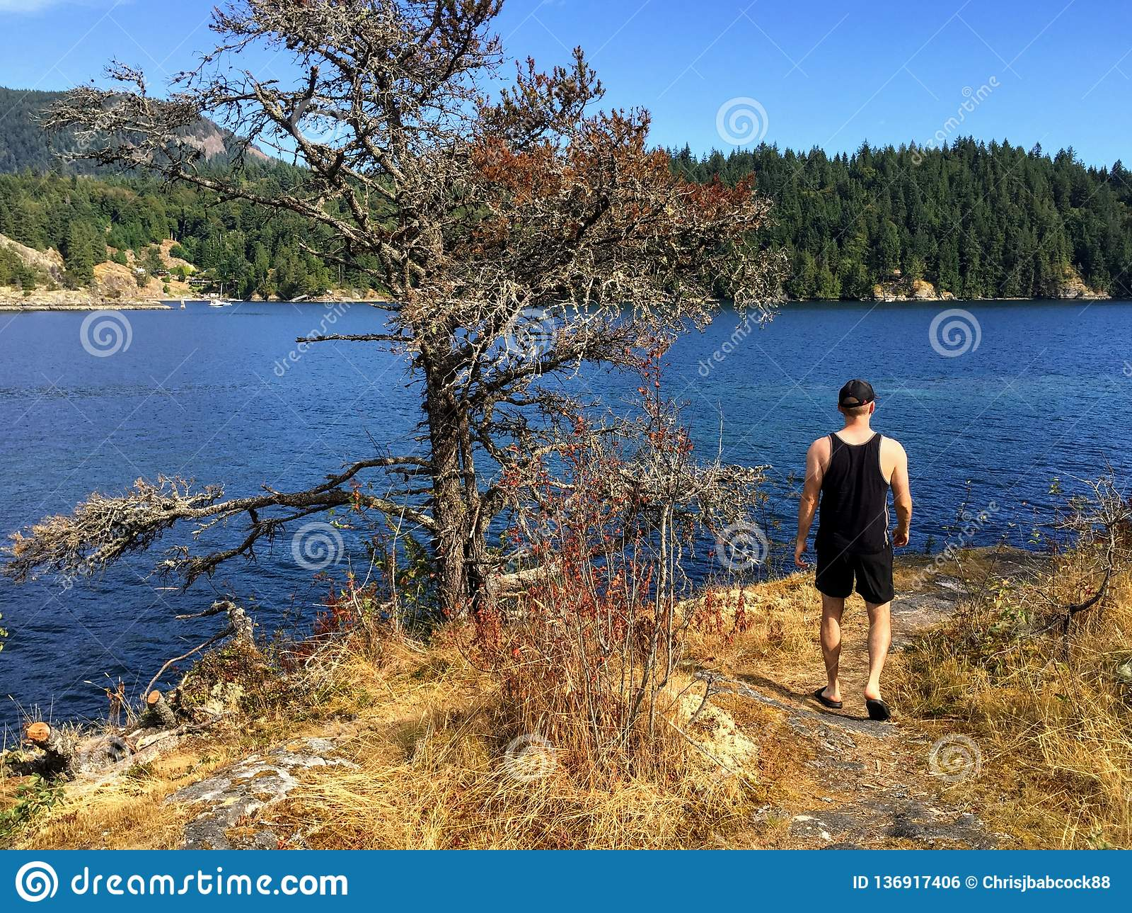 Młodego człowieka odprowadzenie wzdłuż ścieżki mała Aleksander wyspa przegapia ocean zachód zatoka i stały ląd gambir wyspa