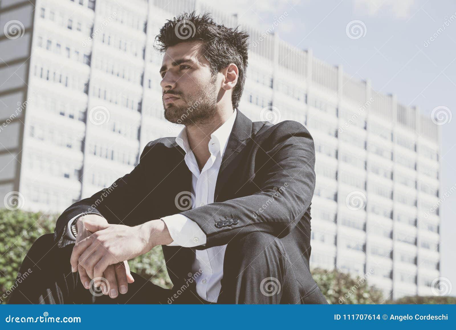 Młodego i przystojnego biznesmena siedzący główkowanie