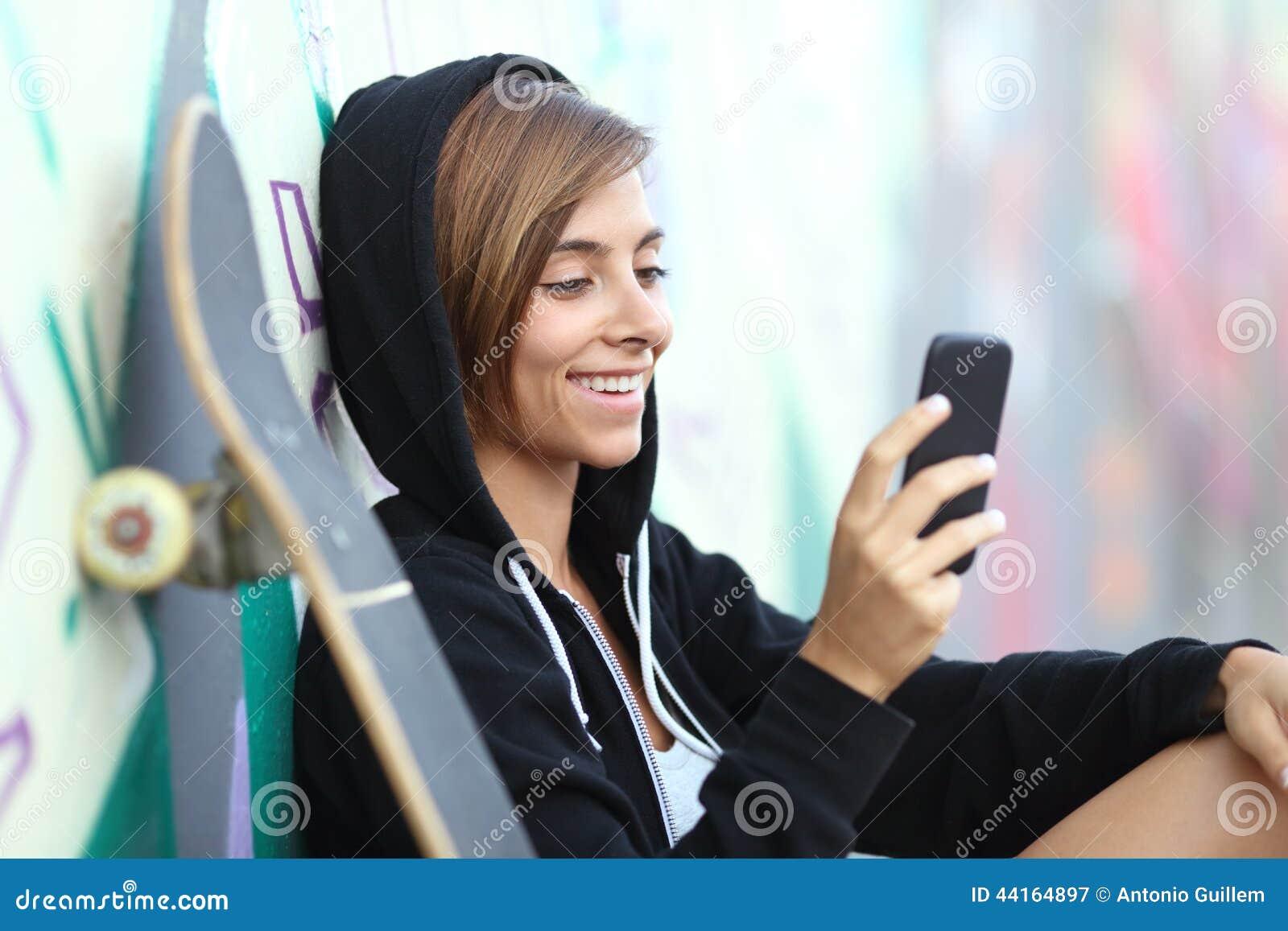 Młodej łyżwiarki szczęśliwa nastoletnia dziewczyna używa mądrze telefon