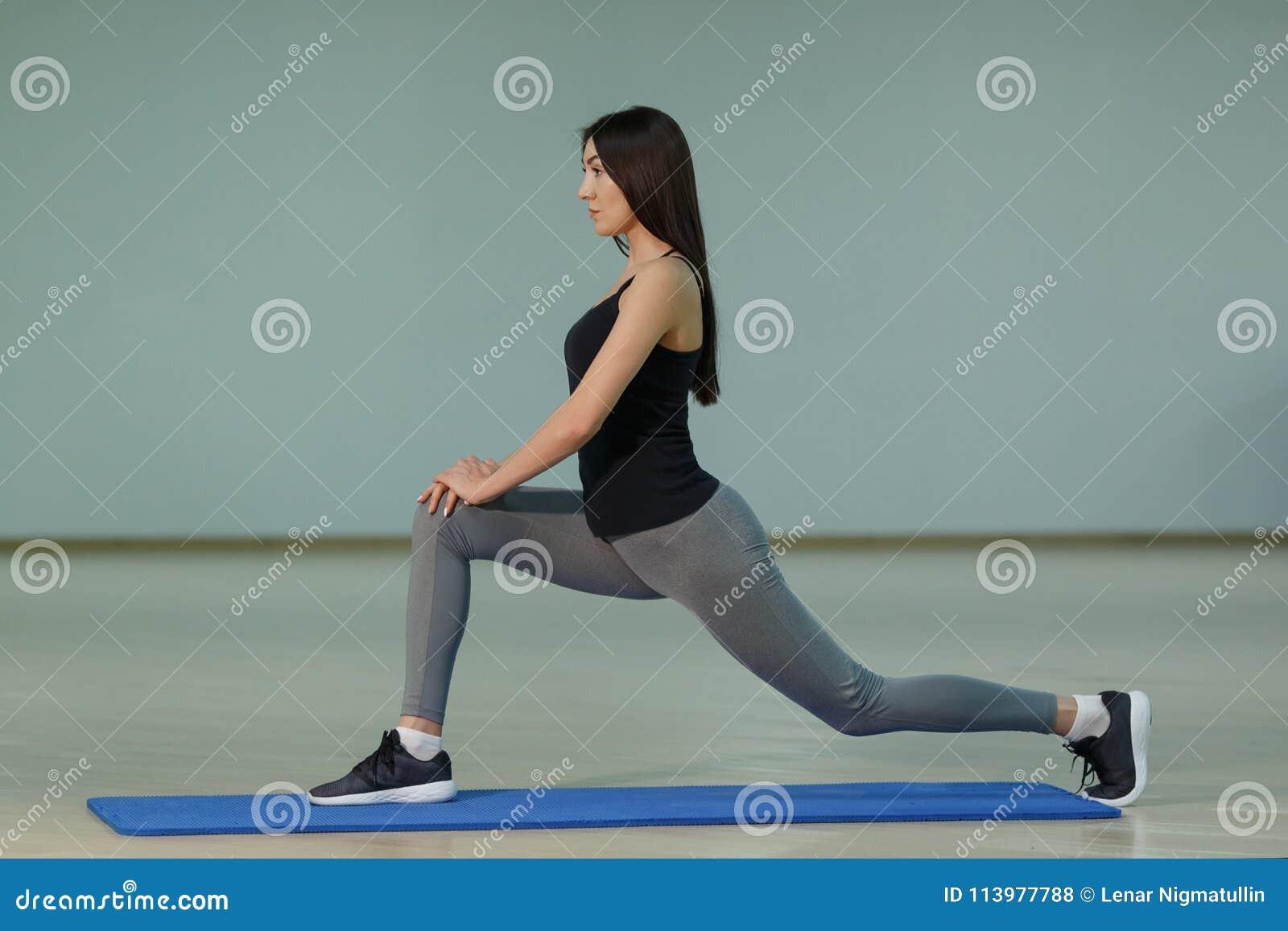 Młodej atrakcyjnej uśmiechniętej kobiety ćwiczy joga na macie w domu