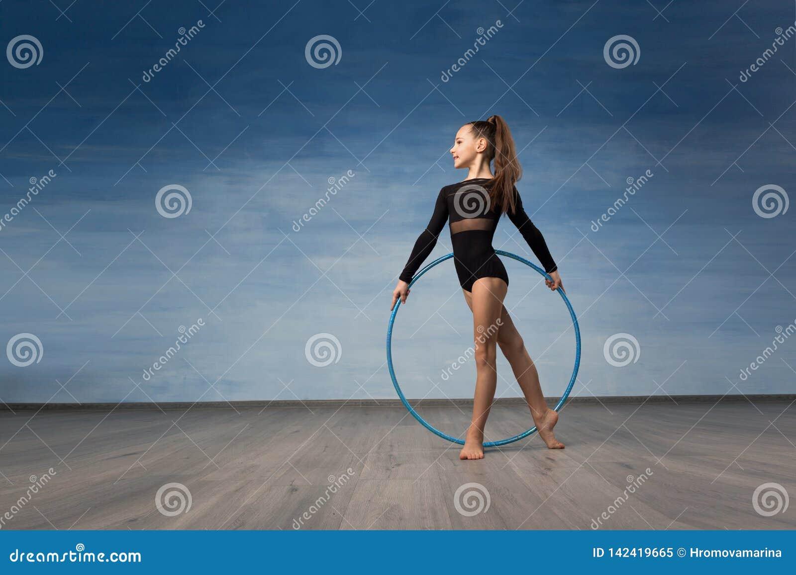 Młodej dziewczyny gimnastyczka w kostiumu kąpielowego czarnych spojrzeniach w profilu w rękach gimnastyczny obręcz
