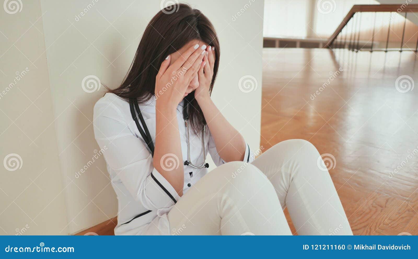 Młodej dziewczyny lekarka płacze obsiadanie na podłoga szpital