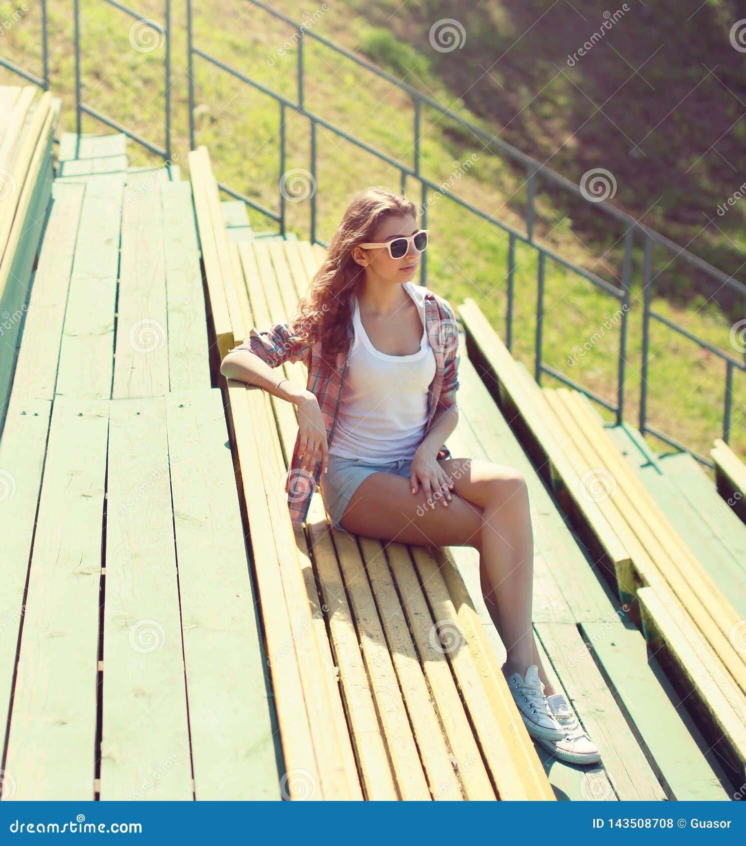 Młodej dziewczyny obsiadanie na ławce w miasto parku na pogodnym lecie