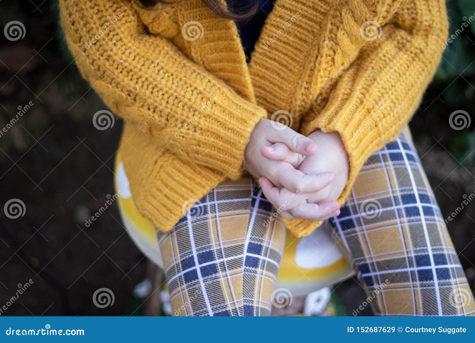 Młodej dziewczyny obsiadanie na stolec mienia rękach