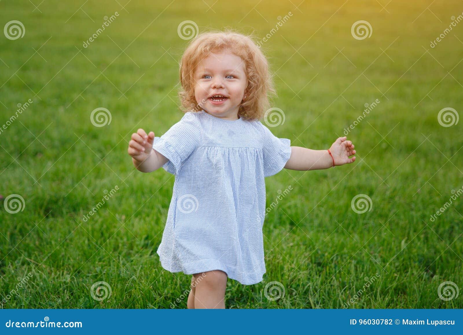 Młodej dziewczyny odprowadzenie na trawy ono uśmiecha się