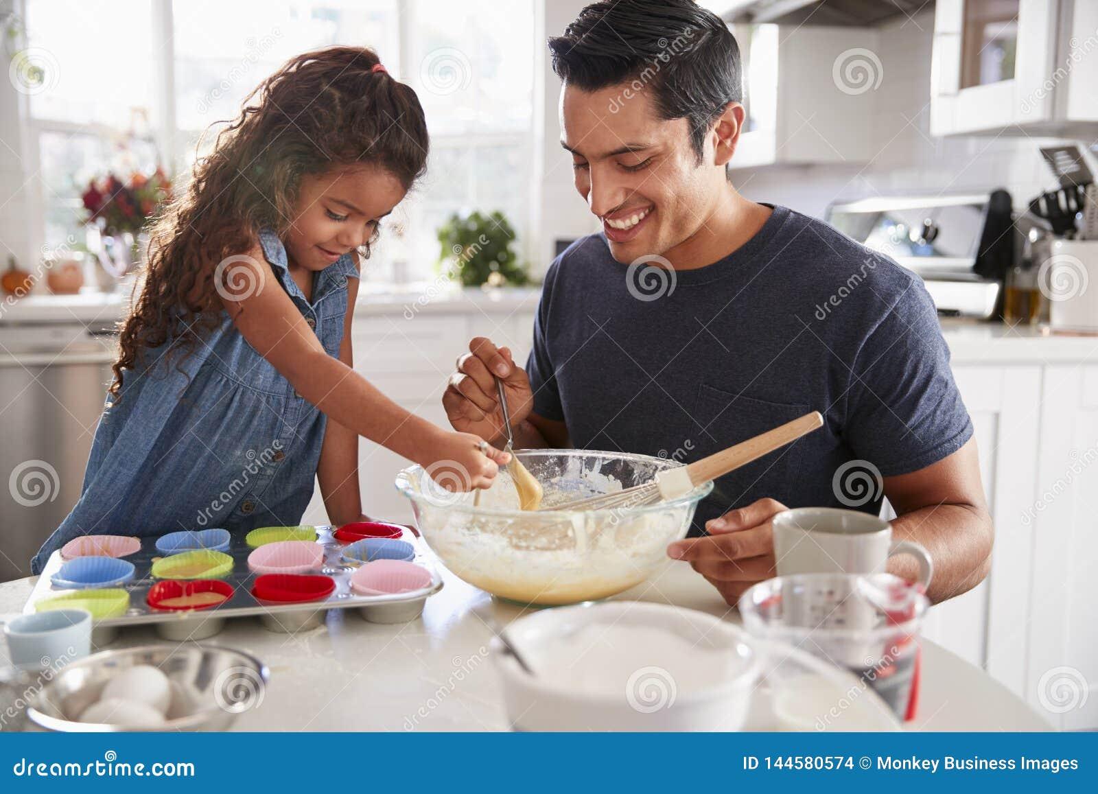 Młodej dziewczyny pozycja przy kuchennym stołem przygotowywa tortową mieszankę z jej ojcem, zakończenie w górę
