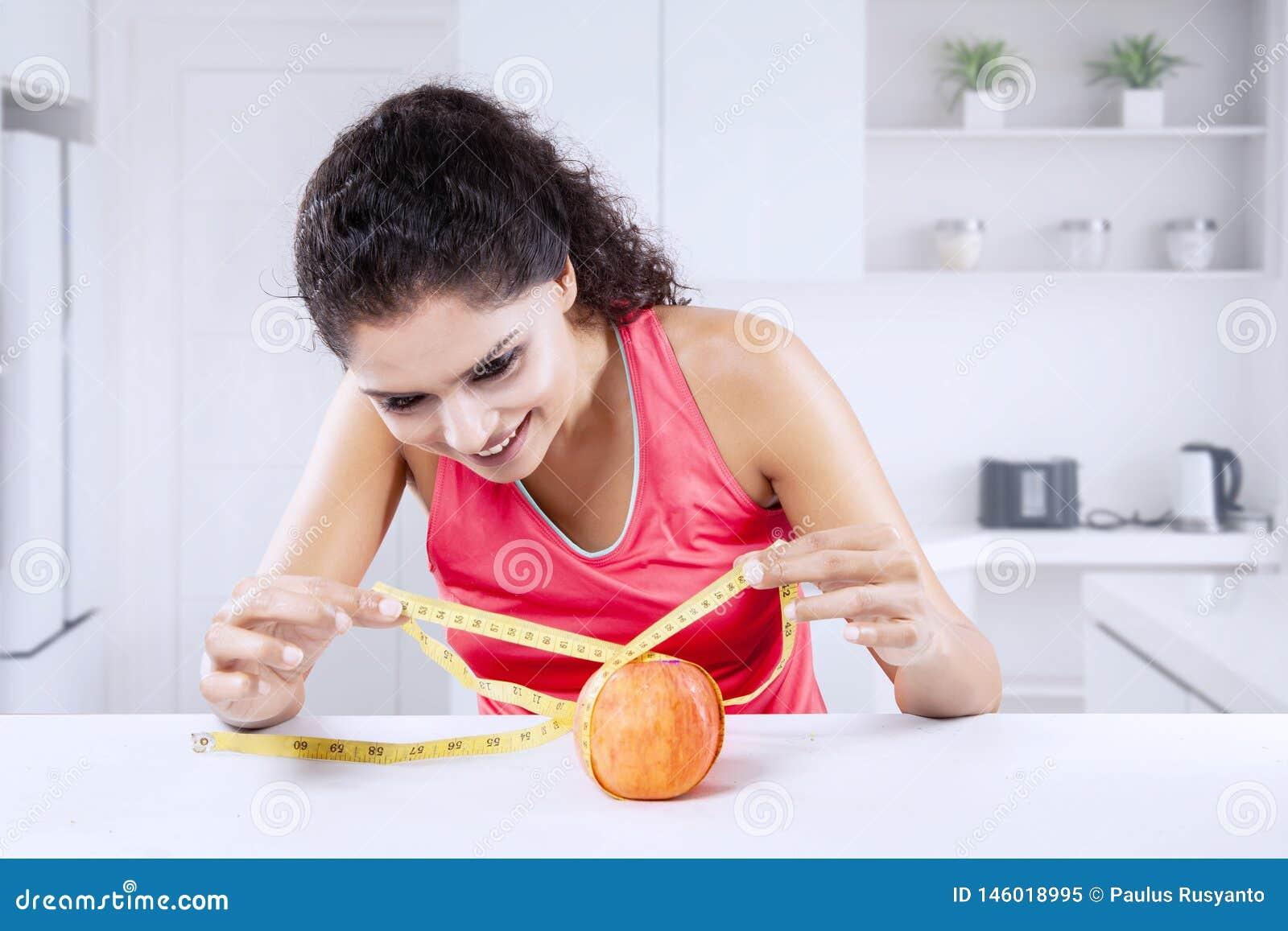 Młodej Indiańskiej kobiety pomiarowy świeży jabłko