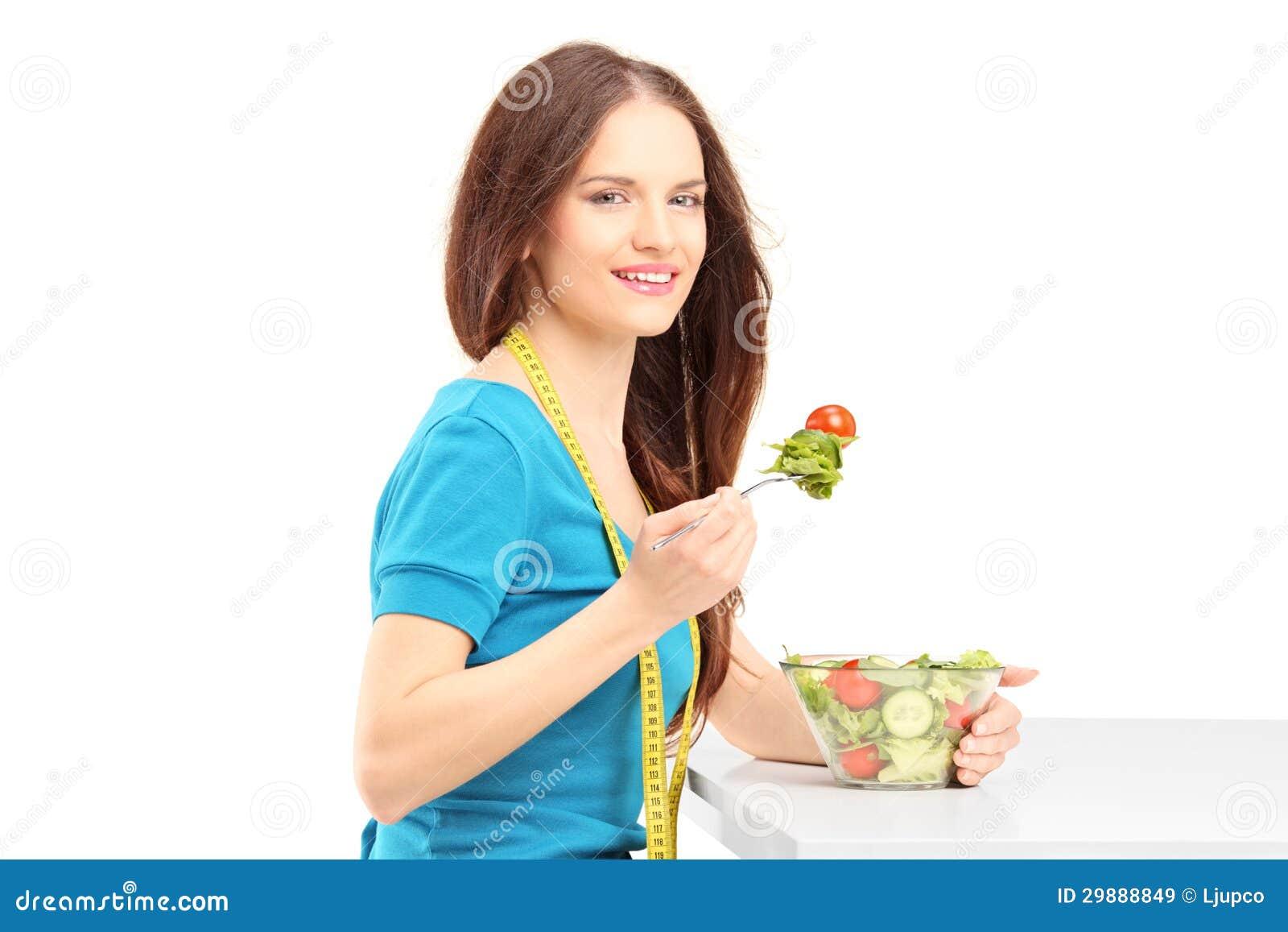 Młodej kobiety łasowanie i obsiadanie świeża sałatka