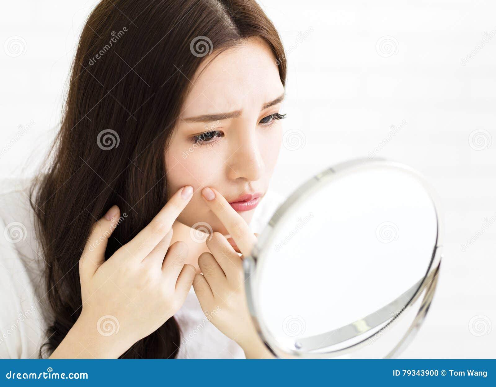 Młodej kobiety ściśnięcie jej trądzik przed lustrem
