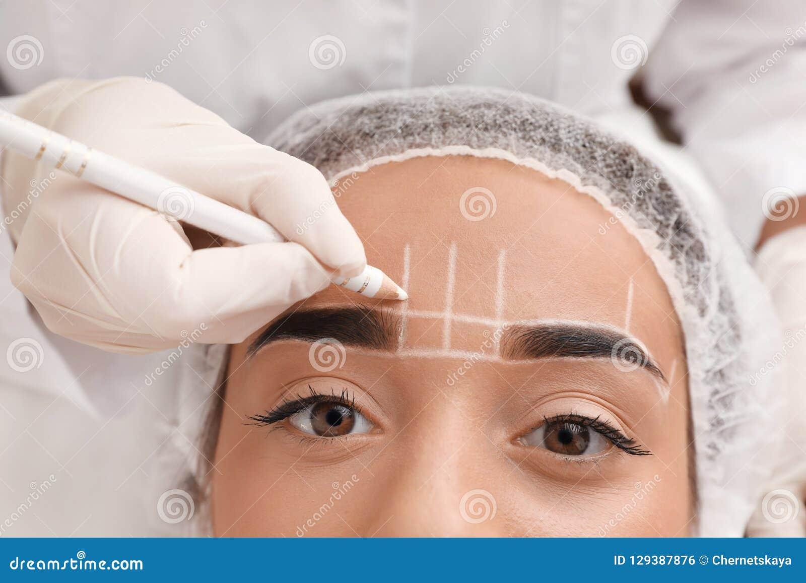 Młodej kobiety dostawać przygotowywał dla procedury stały brwi makeup w tatuażu salonie