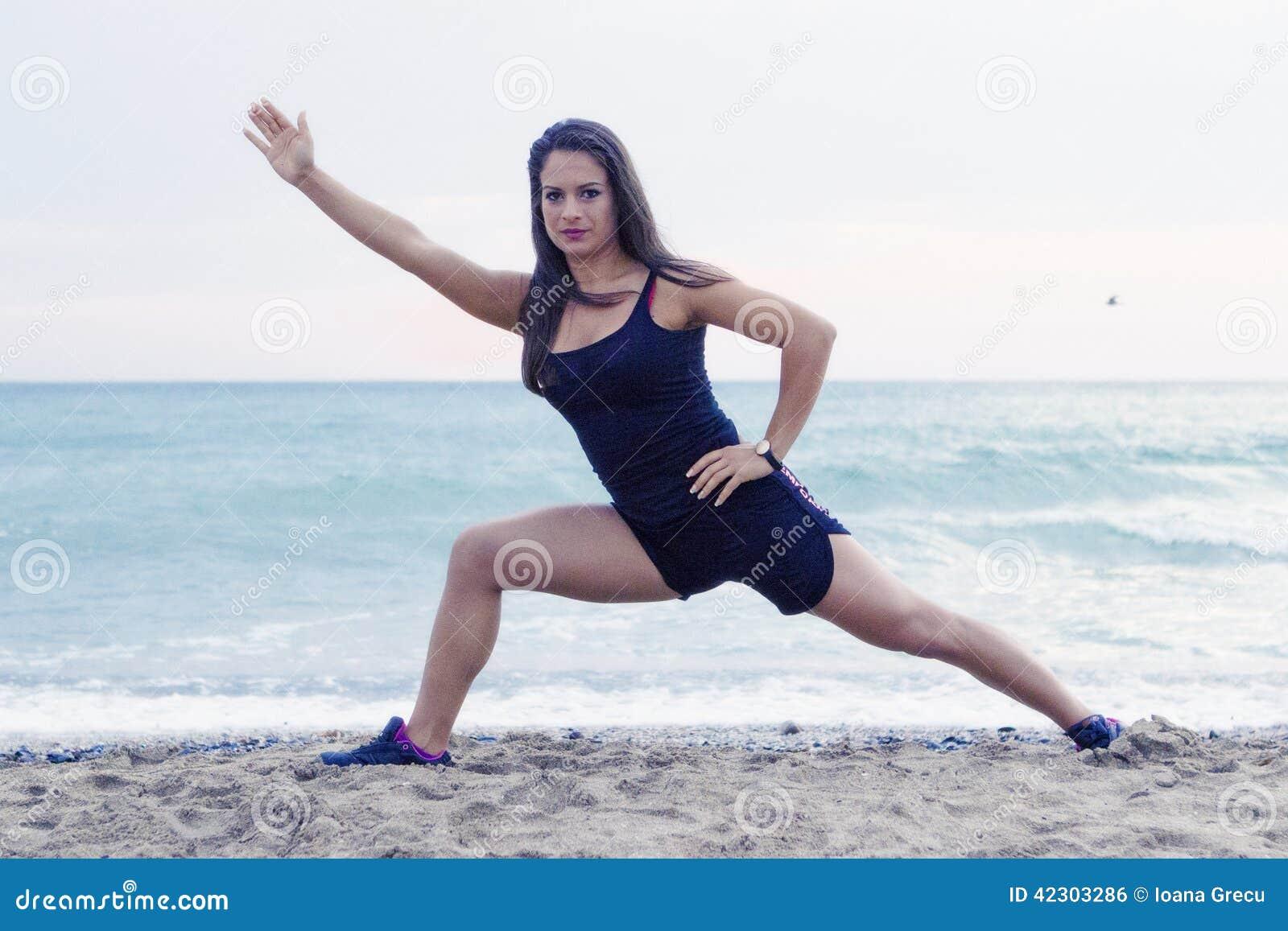 Młodej kobiety iść joga przy plażą