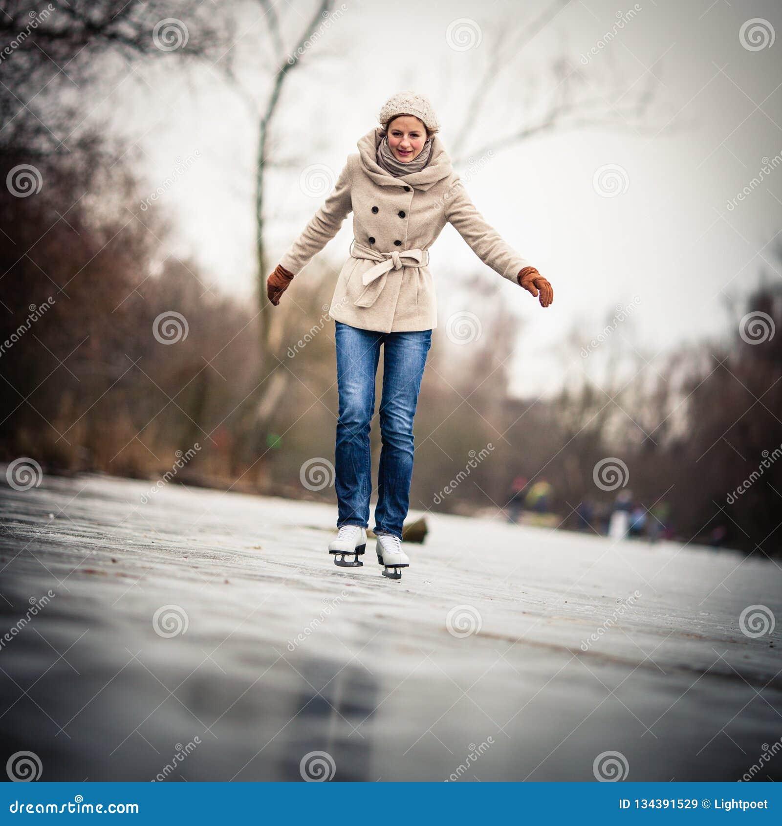 Młodej kobiety jazda na łyżwach outdoors na stawie