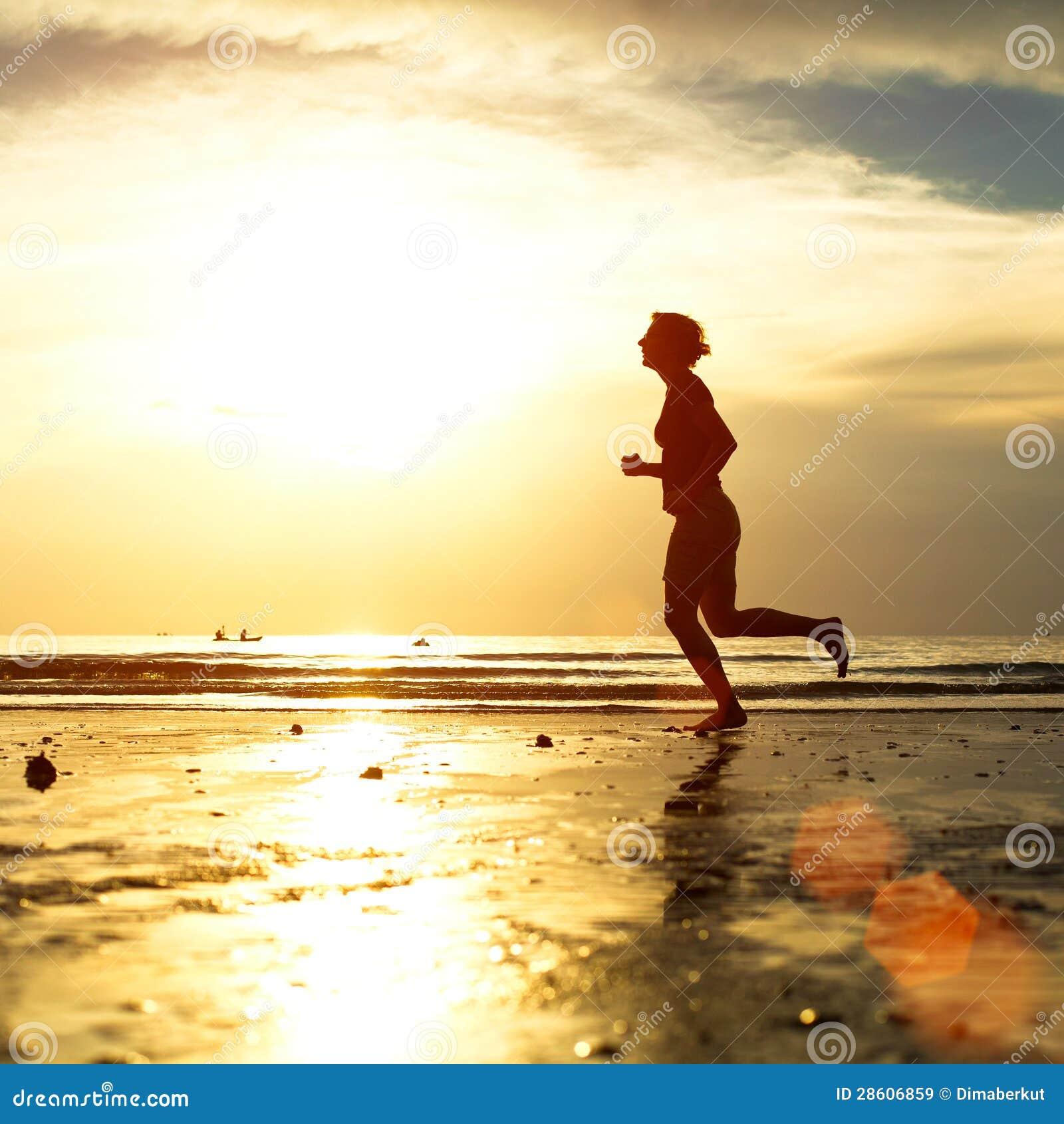 Młodej kobiety jogger przy zmierzchem na seashore