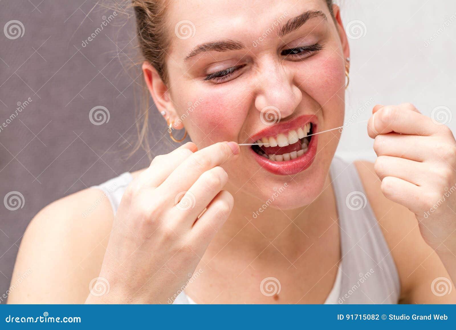 Młodej kobiety kaleczenie herself w używać stomatologicznego floss dla higieny