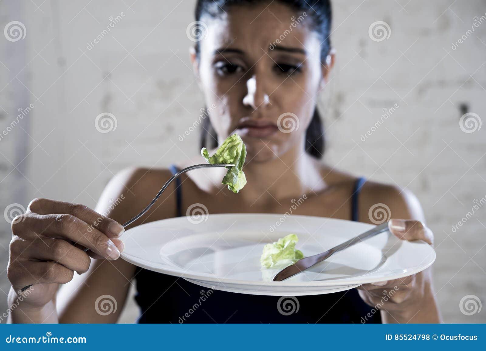 Młodej kobiety mienia naczynie z niedorzeczną sałatą jak jej karmowego symbol szalony diety odżywiania nieład
