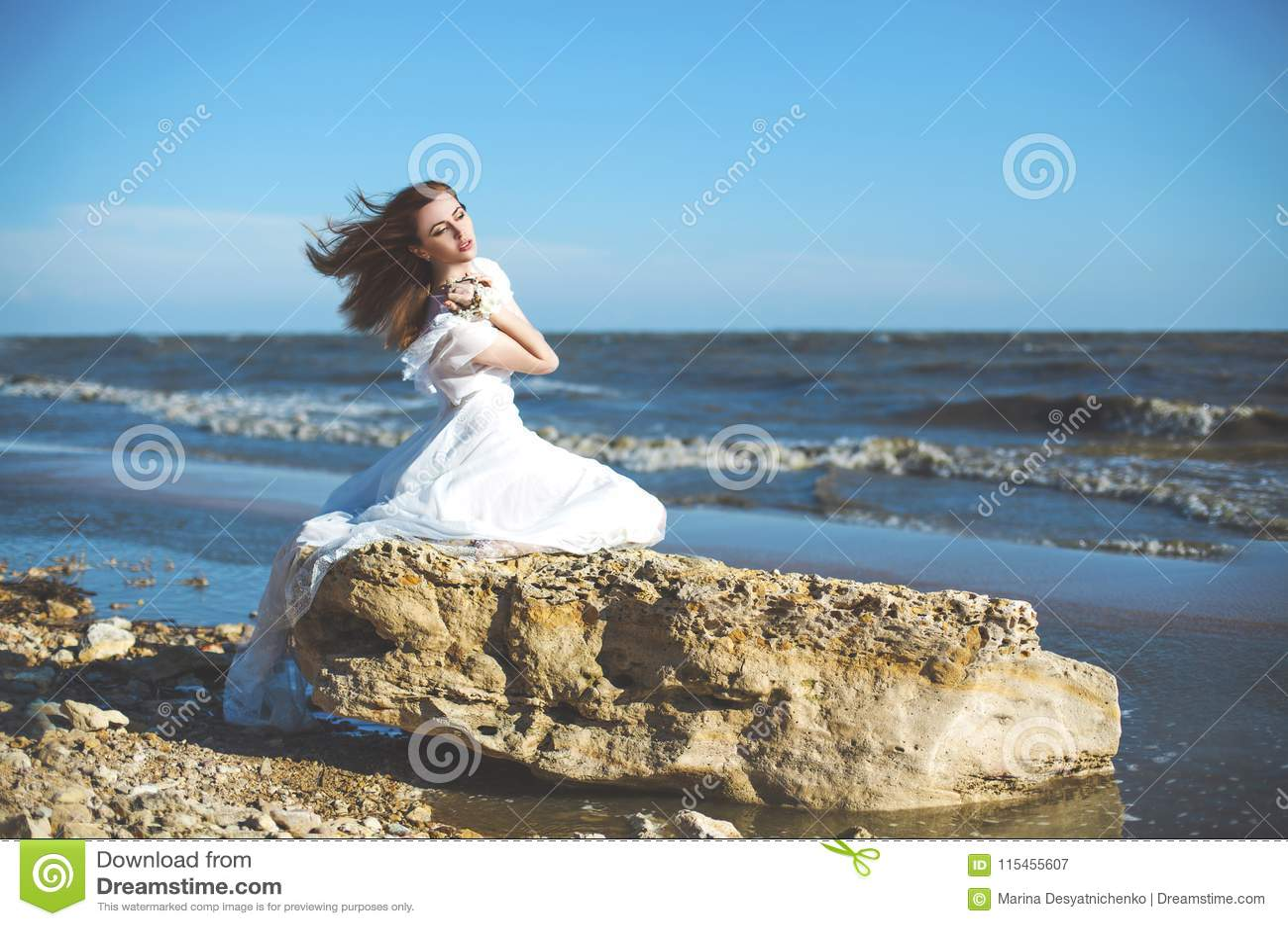 Młodej kobiety obsiadanie na kamieniu na dennym wybrzeżu