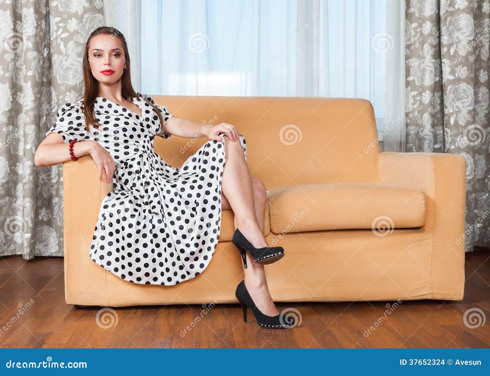 Młodej kobiety obsiadanie na kanapie