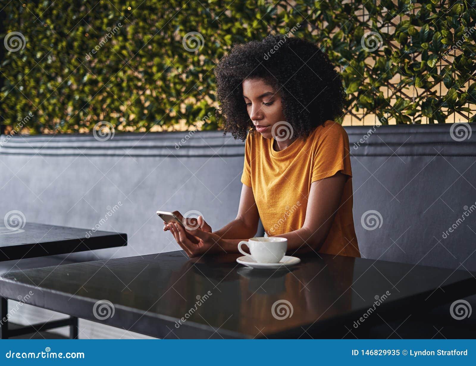 Młodej kobiety obsiadanie w cukiernianym używa telefonie komórkowym