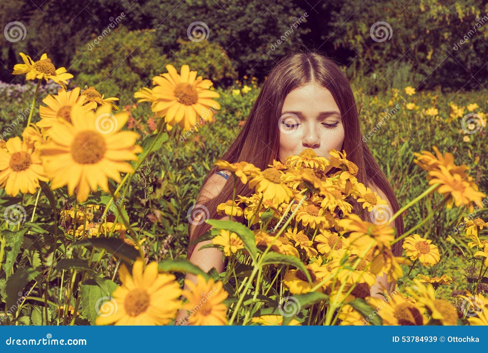 Młodej kobiety obwąchanie kwitnie Heliopsis w ogródzie Fotografia tonująca