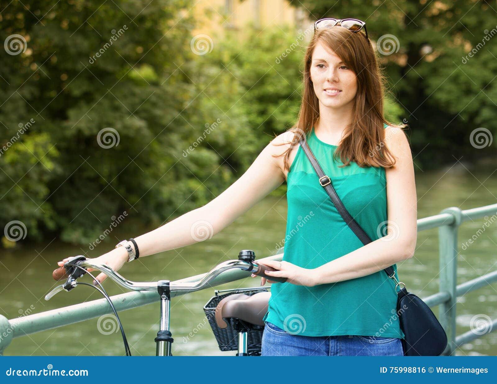 Młodej kobiety odprowadzenie z jej bicyklem rzeką