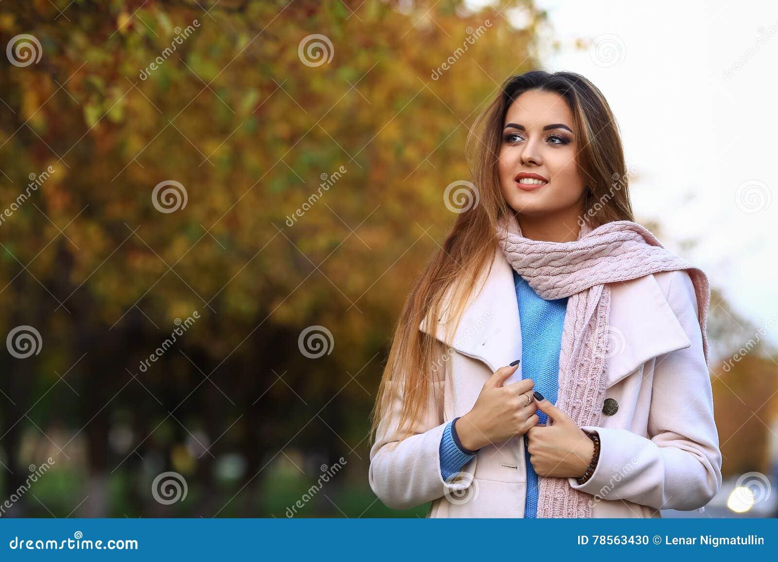 Młodej kobiety ono uśmiecha się i spadku klonu ogródu żółty tło wolna przestrzeń