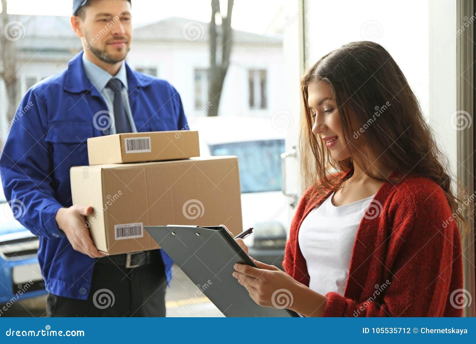 Młodej kobiety podpisywania dokumenty po odbiorczego pakuneczka