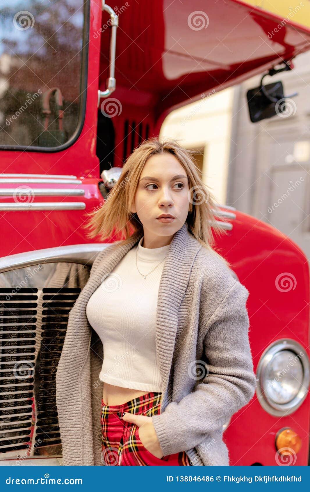 Młodej kobiety pozycja blisko Londyńskiego czerwonego autobusu