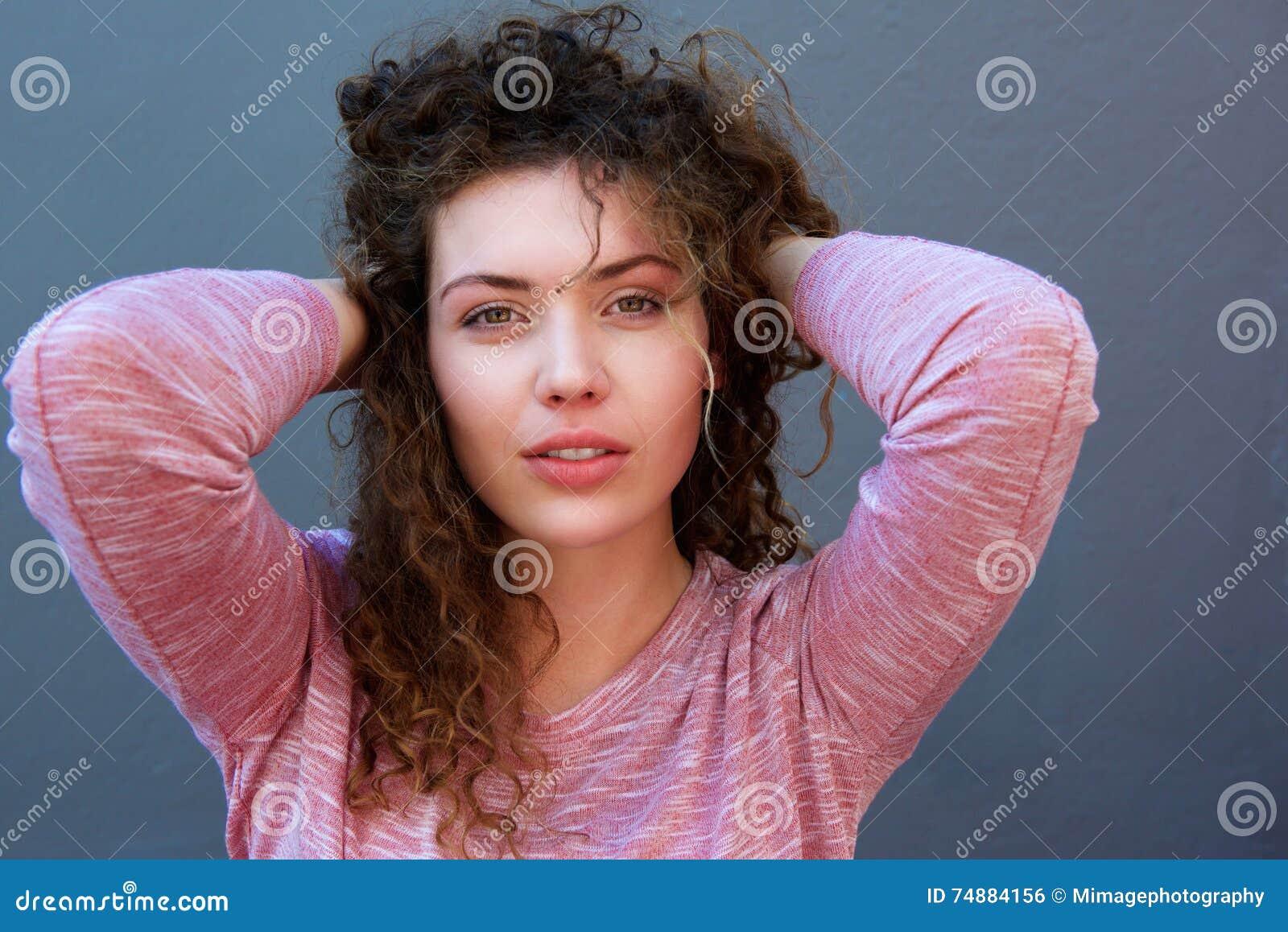Młodej kobiety pozycja z rękami za głową